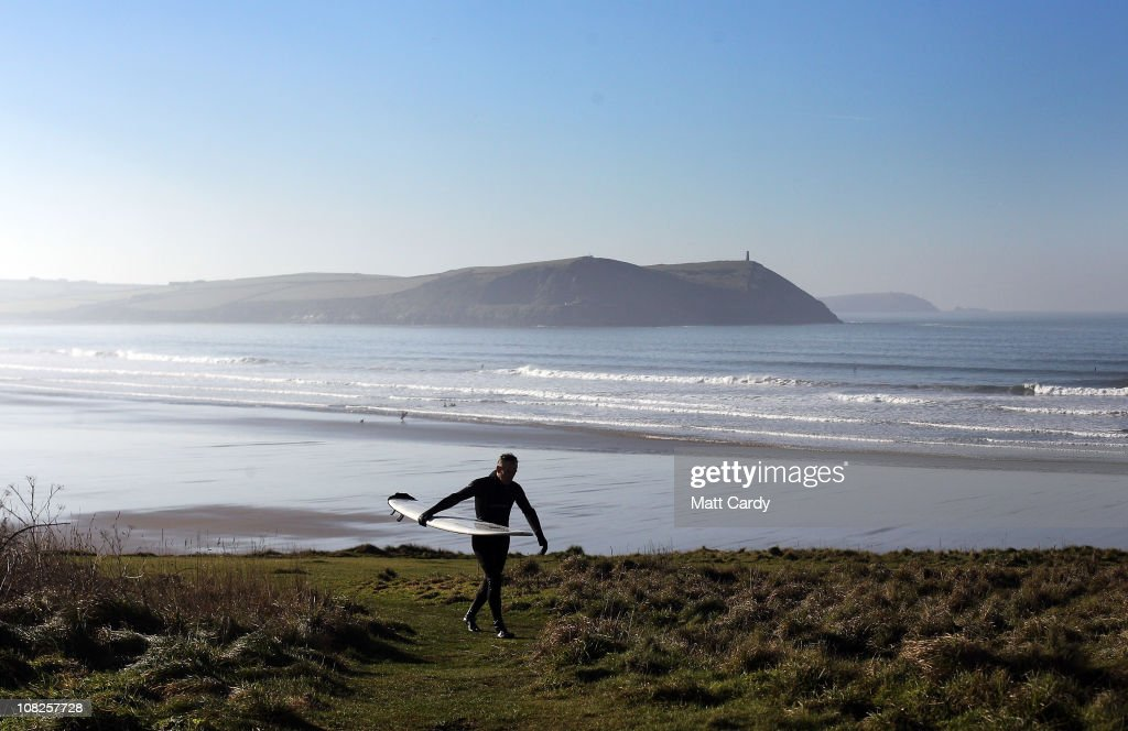 A surfer makes his way from the beach after braving the winter waves on January 20 2011 in Polzeath England Improved wetsuit materials and technology...