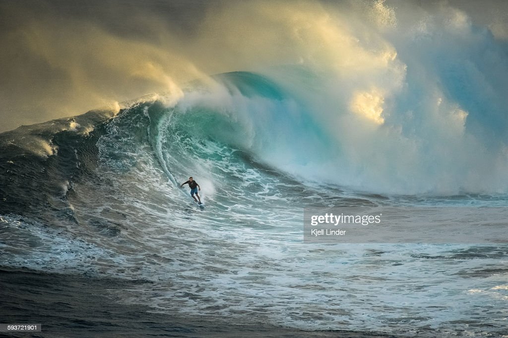 A brave surfer takes on the infamous surf break at Jaws, Maui. The wave is closing out and dumping massive white water behind the surfer. Sunset light comes in from behind the wave.