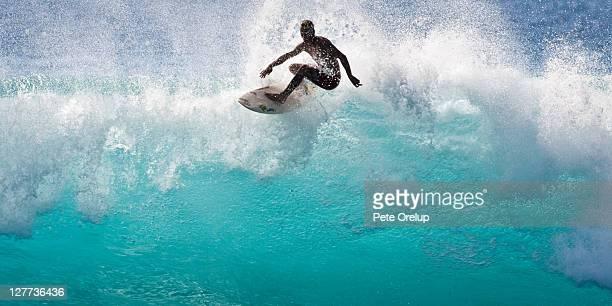 Surfer on backlit wave