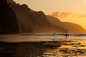 Surfer on beach and Na Pali Coast seen from Ke'e beach, Ha'ena, Kauai, Hawaii