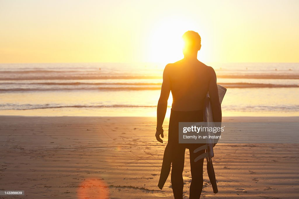 Surfer on beach at sunset : Stock Photo