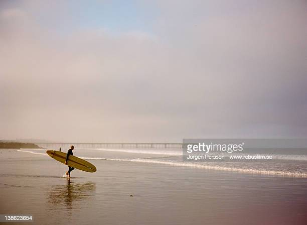 Surfer on beach in morning