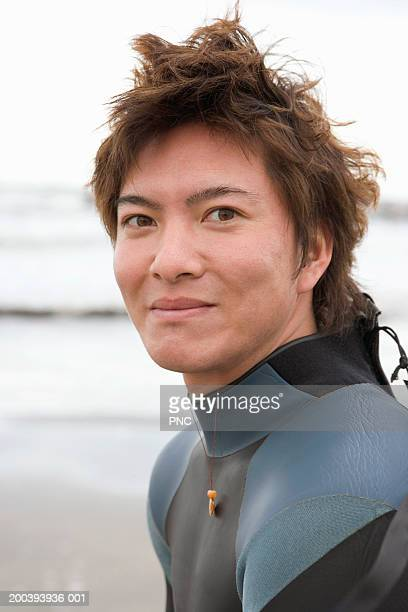 Surfer on beach in wetsuit, Chiba, Japan