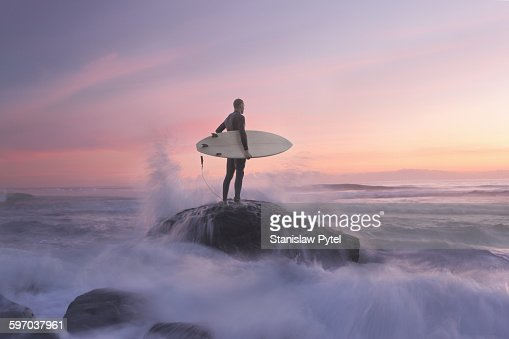 Surfer on rock against sunset, water around
