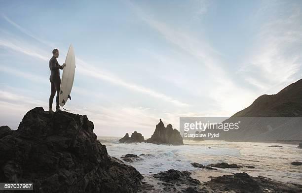 Surfer on rock looking at ocean