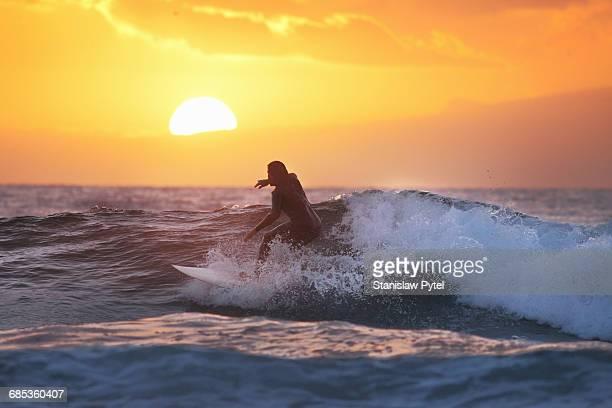 Surfer on wave at sunset