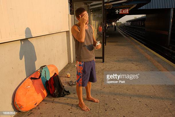 Surfer Paul Treacy applies sun screen while waitng for a train on a New York City Subway platform August 2 2001 during his hourlong trek from his...