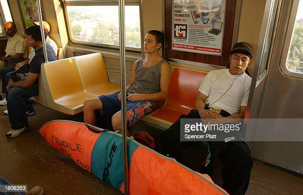 Surfer Paul Treacy rides the New York City Subway with his surfboard August 2 2001 during his hourlong trek from his Manhattan apartment to Rockaway...