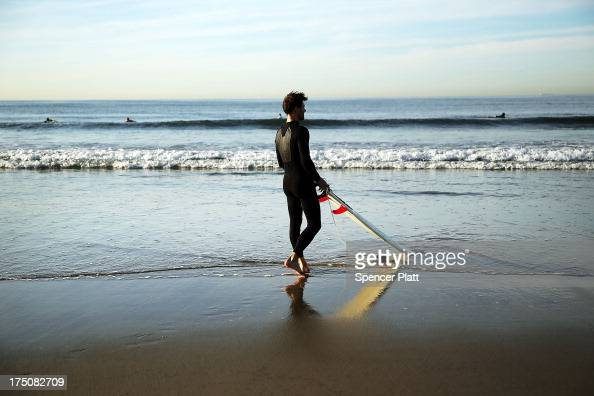 A surfer prepares to go into the water during an early morning surfing session at Rockaway Beach on July 31 2013 in the Queens borough of New York...