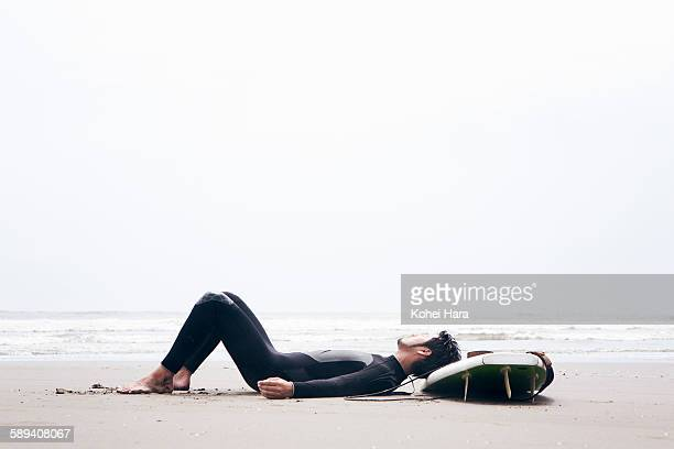 A surfer relaxed on the beach