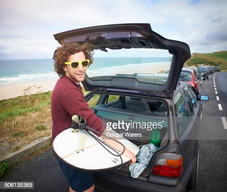 Surfer removing surfboard from car