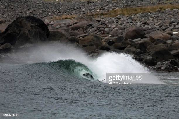 A surfer rides a barrel during the Lofoten Masters 2017 the northernmost surf contest in the world on September 23 2017 in Unstad's Bay in the Arctic...