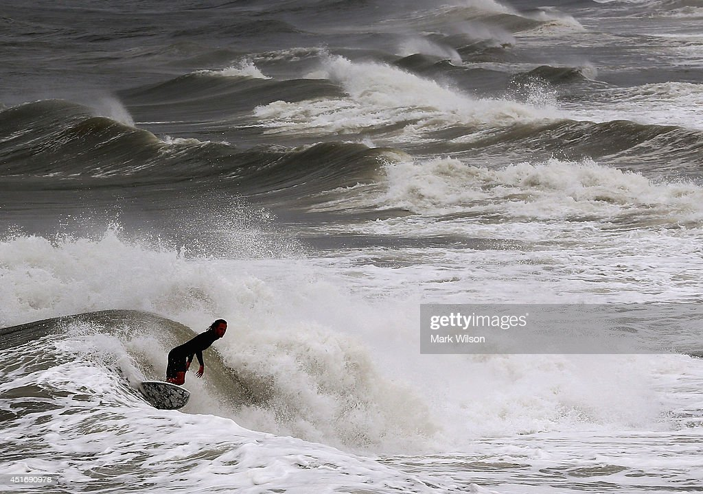 A surfer rides a large wave caused by Hurricane Arthur passing the area during the night, July 4, 2014 in Avalon, North Carolina. Hurricane Arthur hit North Carolina's outer banks overnight causing widespread power outages, flooding and damage, and has since weakened to a Category 1 as of Friday morning.