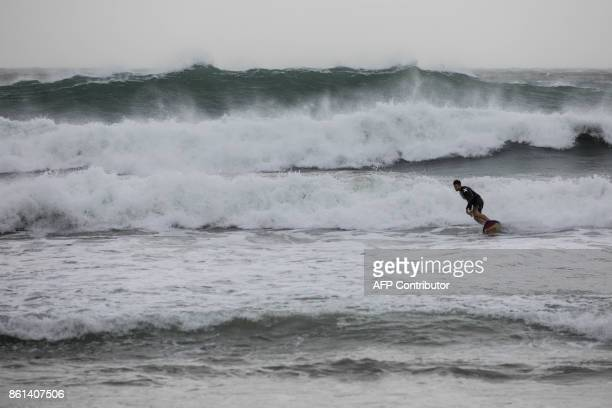 A surfer rides a wave at a beach in Hong Kong on October 15 2017 as Typhoon Khanun moved across the northern part of the South China sea / AFP PHOTO...