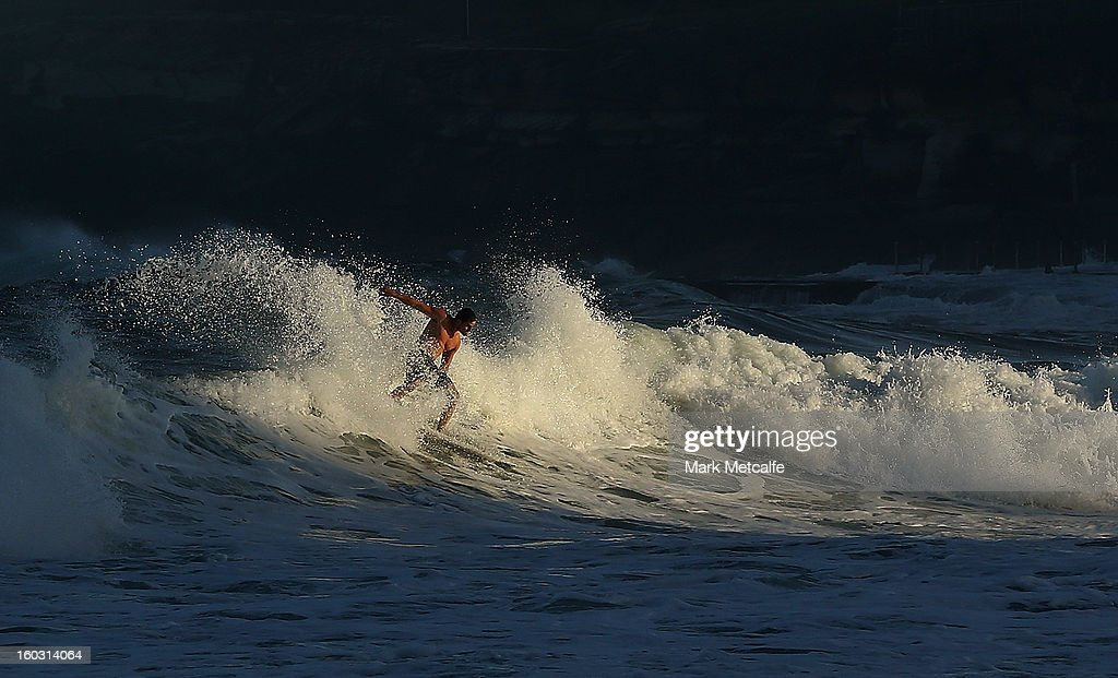 A surfer rides a wave at Coogee Beach after winds and rain battered Sydney last night generating large swell on January 29, 2013 in Sydney, Australia. Parts of Sydney are experienced record rainfall after ex-cyclone Oswald swept through the city last night.