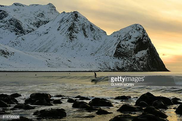 A surfer rides a wave at the end of afternoon at the snowy beach of Unstad in Lofoten archipelago Arctic Circle on March 9 2016 / AFP / OLIVIER MORIN