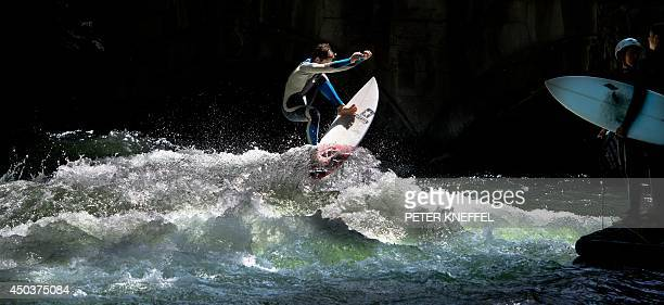 A surfer rides a wave at the Englischer Garten in Munich southern Germany on June 10 2014 AFP PHOTO / DPA / PETER KNEFFEL GERMANY OUT