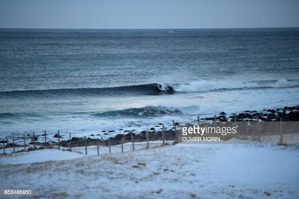 A surfer rides a wave at Unstad along the northern Atlantic Ocean on March 12 where the water temperatures is at five degrees centigrade and the air...