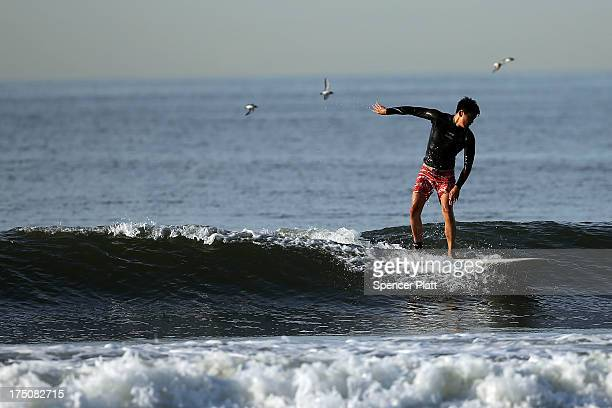 A surfer rides a wave during an early morning surfing session at Rockaway Beach on July 31 2013 in the Queens borough of New York City Despite the...
