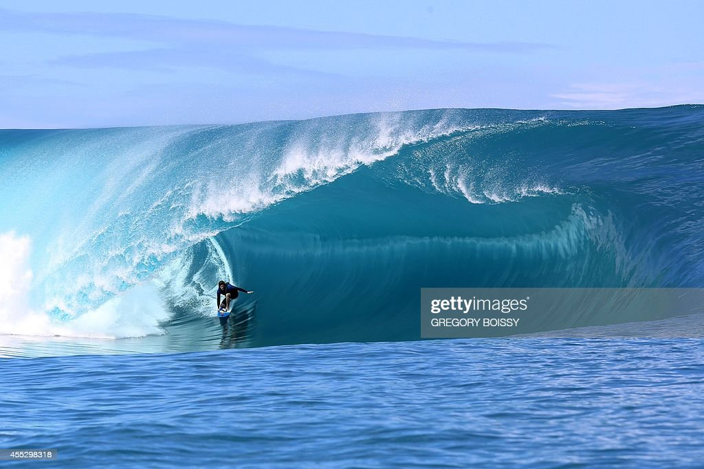 A surfer rides a wave during the shooting of a remake of the 1991 classic 'Point Break' on September 11 2014 in the Hava'e pass in Teahupoo on the...