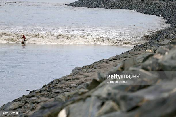 A surfer rides the Bore Tide at Turnagain Arm on July 15 2014 in Anchorage Alaska Alaska's most famous Bore Tide occurs in a spot on the outside of...