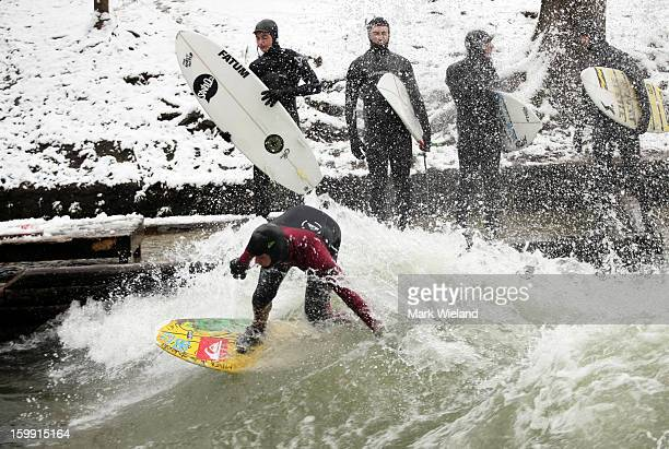 A surfer rides the Eisbach wave in the English Garden on January 13 2013 in Munich Germany The manmade wave at the Eisbach which has been surfed...