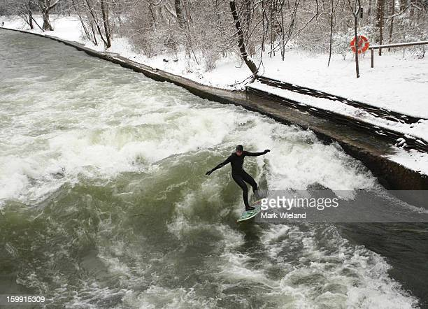 A surfer rides the Eisbach wave on January 19 2013 in Munich Germany The manmade wave at the Eisbach which has been surfed since 1972 officially...