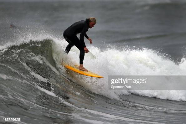 A surfer rides the morning waves at Rockaway beach on October 9 2013 in the Queens borough of New York City Nearly one year after Hurricane Sandy...
