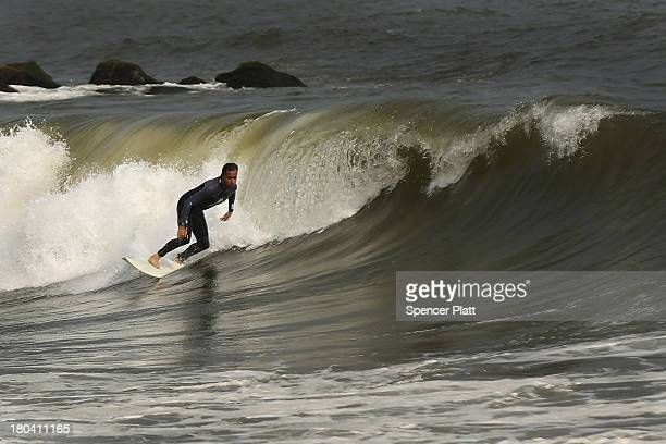 A surfer rides waves in the in the late afternoon at Rockaway Beach on September 12 2013 in the Queens borough of New York City Despite the sustained...