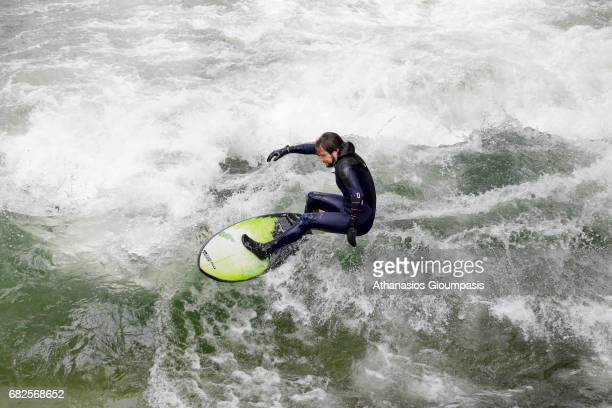 Surfer riding a wave in a stream in the Eisbach at Englischer Garten on April 13 2017 in Munich GermanyThe wave has been surfed by river surfers...