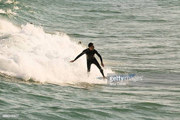 Surfer riding a wave in the Mediterranean Sea during the sunset light Vilassar de Mar Catalonia Europe 12th June of 2015