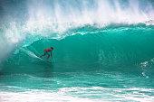 Surfer riding extremely big wave at Padang Padang beach, Bali, Indonesia. Beautiful green water falling behind, copy space