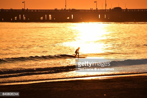 A surfer riding on mild wave in the sunset beach : ストックフォト