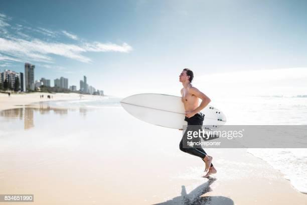 surfer running on surfers paradise beach in australia