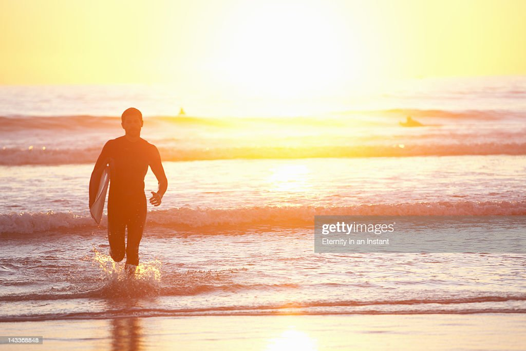 Surfer running out of  ocean at sunset : Stock Photo