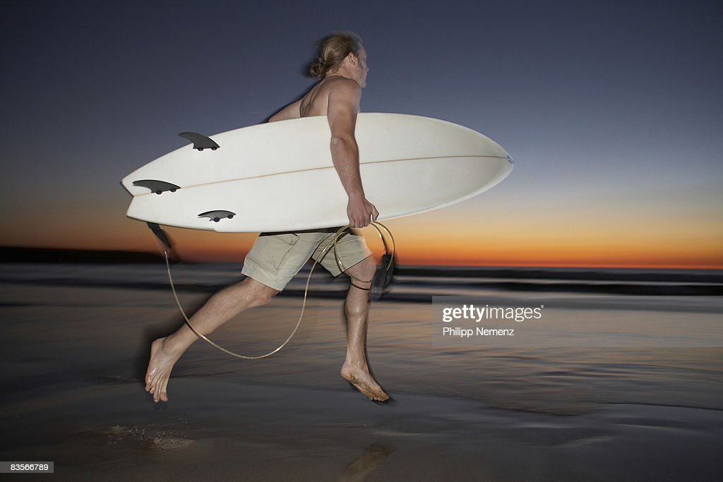 Surfer running with Board on Beach at Sunset : Stock Photo