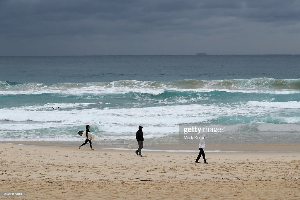 A surfer runs along the sand near visitors dressed in winter clothing to combat the cold temperatures at Bondi Beach on June 27, 2016 in Sydney, Australia. Sydney experienced its coldest day of the year on Sunday, and more icy weather is forecast for later in the week when a second cold front hits later in the week.