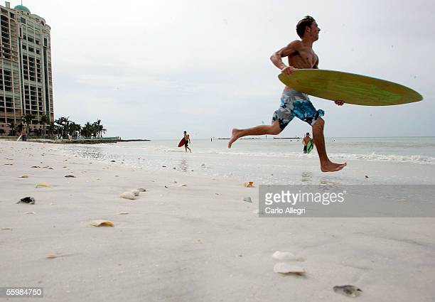 A surfer runs into the water in advance of the arrival of Hurricane Wilma October 22 2005 in Marco Island Florida Wilma is expected to make landfall...