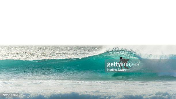 Surfer silhouette on blue wave