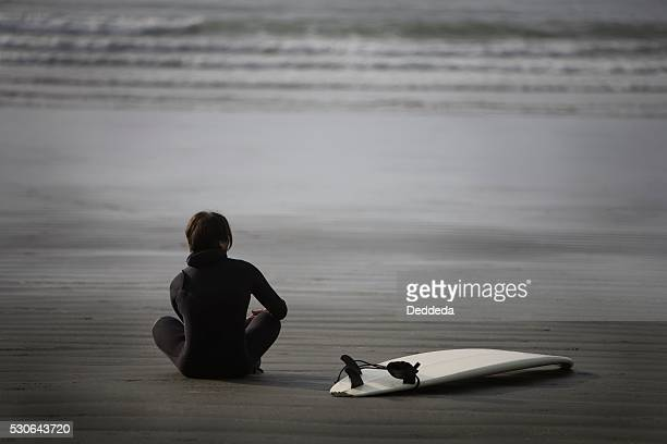 Surfer sitting on beach, Cox Bay near Tofino, British Columbia, Canada