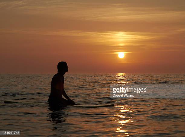 Surfer sitting on board at sunset.