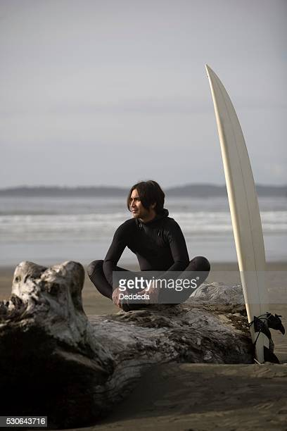 Surfer sitting on log on beach, Cox Bay near Tofino, British Columbia, Canada