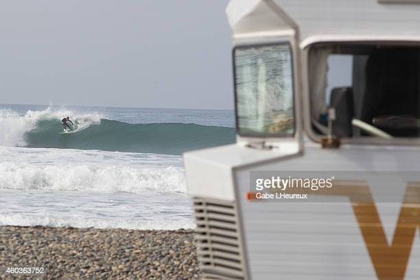 A surfer slashes a large wave crashing while an RV is parked in the foreground on December 11 2014 in San Diego California