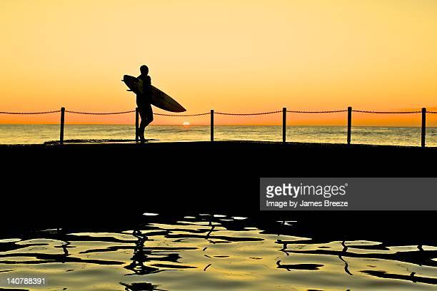 Surfer standing edge of pool at sunset