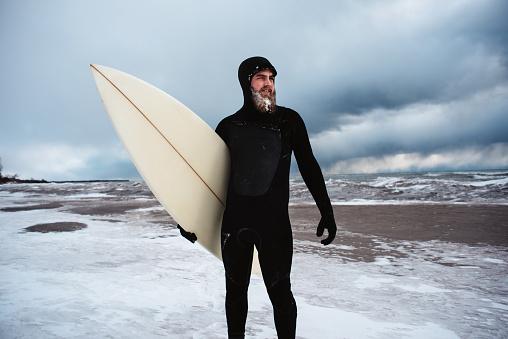 Surfer standing in Lake Ontario in winter