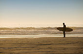 Surfer standing on beach