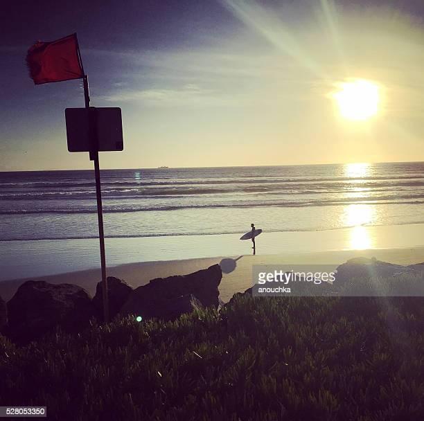 Surfer standing on Coronado Island Beach, San Diego, USA