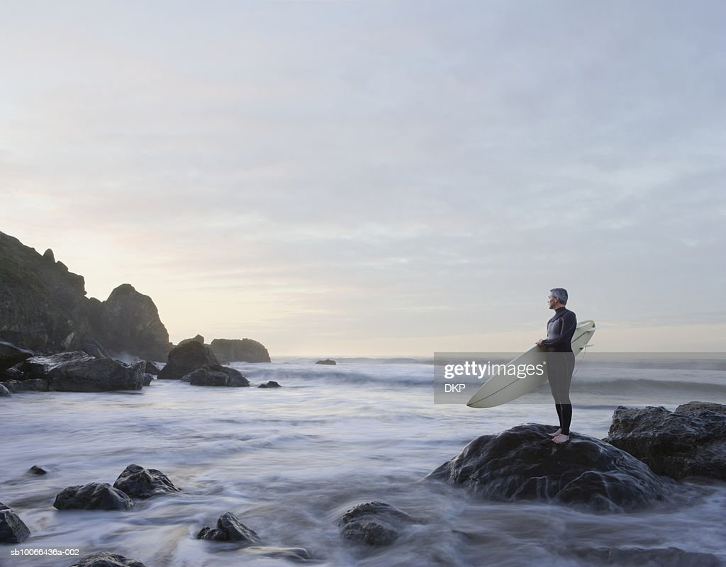 Surfer standing on rock in ocean : Stock Photo
