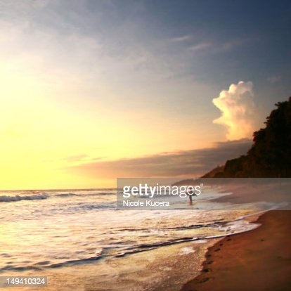 Surfer stands in ocean watching sunset on beach