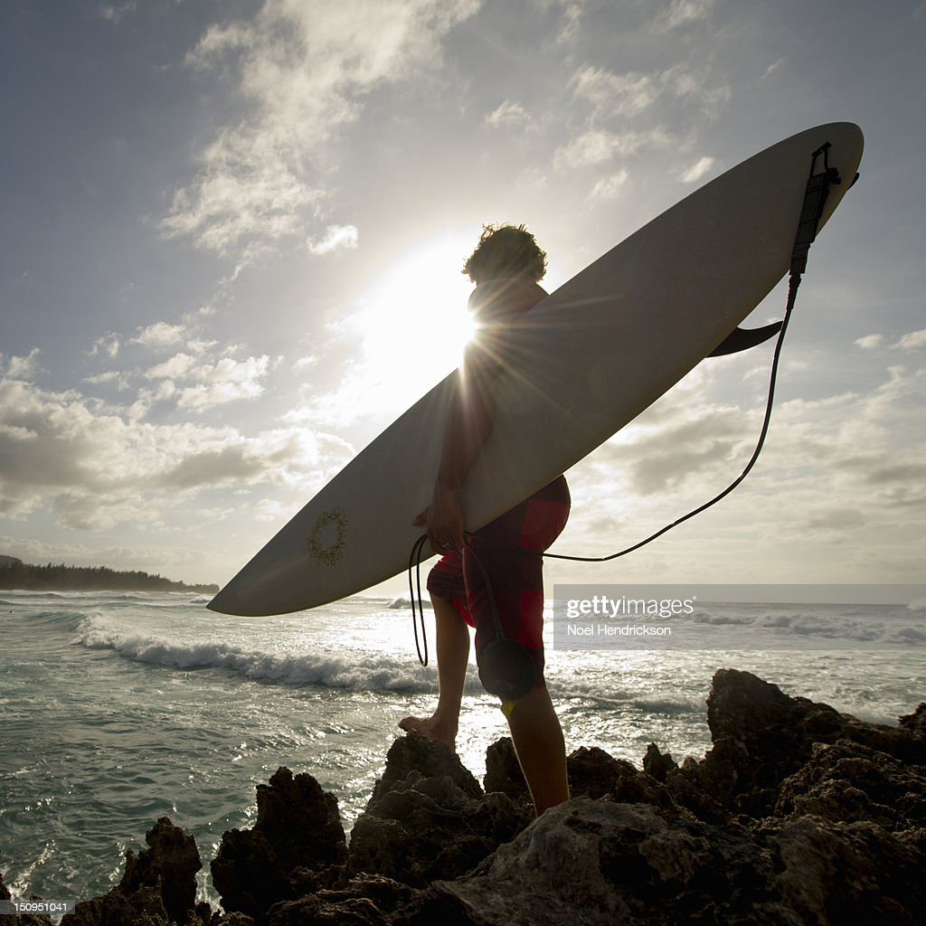 A surfer stands on a rock and looks at the waves : Stock Photo